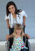 Portrait of a little girl on a wheelchair and a young doctor — Stock Photo