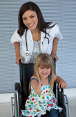 Young female doctor and Smiling girl on a wheelchair with thumb — Stock Photo