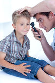 Doctor examining a patient' s ears with a otoscope — Stock Photo