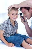 Doctor checking a patient' s ears — Stock Photo