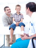 Doctor bandaging a patient's foot with his father — Stock Photo