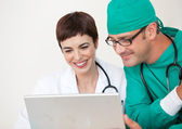 Doctor and surgeon looking at a laptop — Stock Photo