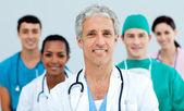 Senior arts staande voor zijn team — Stockfoto