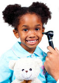 Smiling little girl attending medical check-up holding a teddy b — Stock Photo