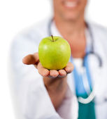 Close-up of a doctor presenting a green apple — Stock Photo