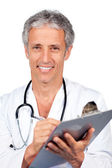 Smiling doctor writting documents — Stockfoto
