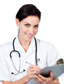 Smiling female doctor writing on a clipboard — Stock Photo
