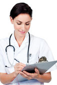 Serious female doctor writing on a clipboard — Stock Photo