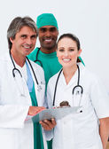 Smiling doctors and surgeon taking notes — Stock Photo