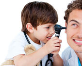 Cute child checking doctor's ears — Stock Photo