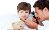 Concentrated doctor examining patient's ears — Stock Photo