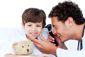 Smiling doctor examining patient's ears — Stock Photo