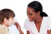 Smiling doctor taking child's temperature — Stock Photo