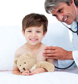 Mature doctor checking little boy's pulse — Stock Photo