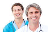 Confident doctors smiling at the camera — Stock Photo