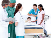 Positive medical team taking care of a little boy — Stock Photo