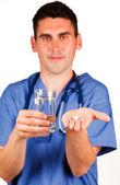 Läkare som innehar ett piller och ett glas vatten — Stockfoto