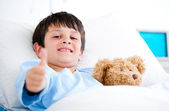 Little boy hugging a teddy bear lying in a hospital bed — Stock Photo