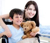 Sorridente menino em uma cadeira de rodas com sua mãe — Foto Stock