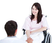 Smiling female patient in a wheelchair interacting with her doct — Stock Photo