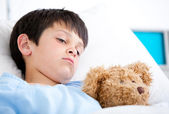 Portrait of a sick boy lying in a hospital bed — Stock Photo