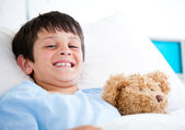 Smiling little boy lying in a hospital bed — Stock Photo