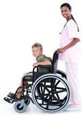 Assertive female doctor carrying a patient in a wheelchair — Stock Photo