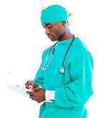 Charismatic male surgeon making notes in a patient's folder — Stock Photo