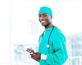 Attractive surgeon making notes in a patient's folder — Stock Photo