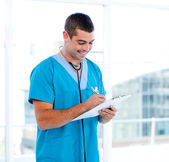 Concentrated male doctor making notes in a patient's folder — Stock Photo