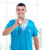 Positive male doctor holding a stethoscope — Stock Photo