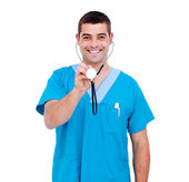 Handsome male doctor holding a stethoscope — Stock Photo