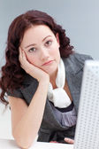 Young businesswoman in front of a computer getting bored — Stock Photo