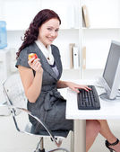 Businesswoman holding an apple in office — Stock Photo