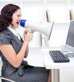 Businesswoman yelling through a megaphone — Stock Photo