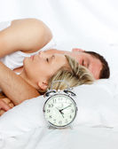 Pár v posteli s fokusem v budík — Stock fotografie