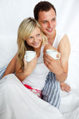 Couple in bed drinking coffee — Stock Photo