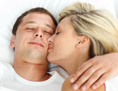 Girlfriend kissing her boyfriend in bed — Stock Photo
