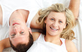 Happy couple resting in bed — Stock Photo
