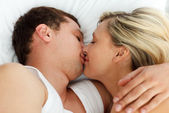 Amorous couple kissing in bed — Stock Photo