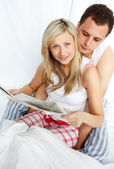 Couple reading a newspaper in bed — Stockfoto