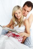 Couple en lisant un journal dans le lit — Photo