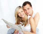 Couple reading a newspaper in bed and smiling at the camera — Stockfoto