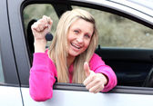 Happy female driver showing a key after bying a new car — Foto Stock