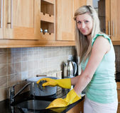 Smiling young woman cleaning in a kitchen — Stock Photo