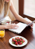 Blond woman using a laptop while having breakfast — Stock Photo