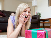 Surprised woman opening gifts lying on the floor — Stock Photo