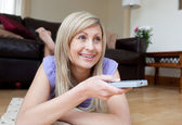 Joyful woman watching TV lying on the floor — Stock Photo