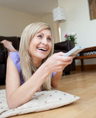 Laughing woman watching TV lying on the floor — Stock Photo