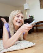 床に横たわってテレビを見て笑う女性 — ストック写真